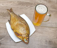 Smoked bream and a glass of beer on a wooden table Royalty Free Stock Images