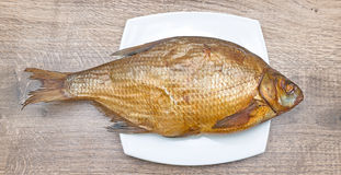 Smoked bream on a plate on wooden background Stock Photography