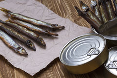 Smoked capelin and conserve tins on wooden background Royalty Free Stock Photography