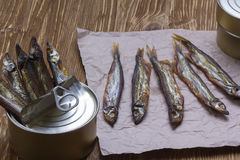 Smoked capelin and conserve tins on wooden background Stock Photo