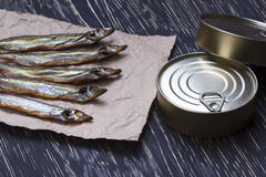 Smoked capelin and conserve tins on wooden background. Smoked capelin and conserve tins on dark wooden background Stock Photography
