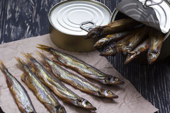 Smoked capelin and conserve tins on wooden background. Smoked capelin and conserve tins on dark wooden background Royalty Free Stock Image