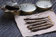 Smoked capelin and conserve tins on wooden background Royalty Free Stock Images