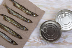 Smoked capelin and conserve tins on wooden background Royalty Free Stock Photos
