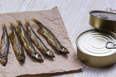 Smoked capelin and conserve tins on wooden background Royalty Free Stock Image