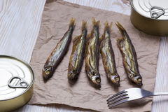 Smoked capelin and conserve tins on wooden background Stock Image