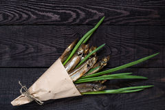 Smoked capelin with green onions in paper cornet Stock Photos