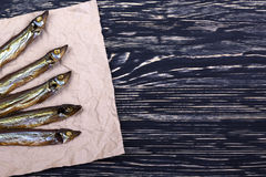 Smoked  capelin on vintage wooden background, top view Stock Photos