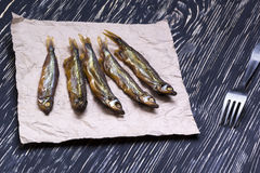 Smoked  capelin on vintage wooden background, top view Royalty Free Stock Photography