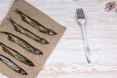 Smoked  capelin on vintage wooden background, top view Royalty Free Stock Images