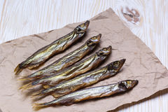 Smoked  capelin on vintage wooden background, top view Royalty Free Stock Photos
