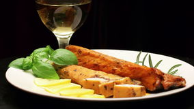 Smoked carp with aromatic herbs and lemon on white plate, rotating stock video footage
