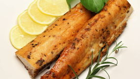Smoked carp with aromatic herbs and lemon on white plate, rotating stock video