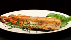 Smoked carp with aromatic herbs on white plate, rotating stock video footage