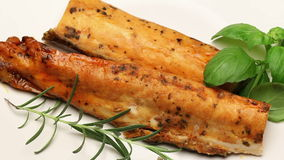 Smoked carp with aromatic herbs on white plate, rotating stock video