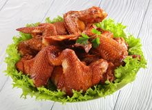Smoked chicken wings with lettuce salad. Delicious crispy smoked chicken wings with lettuce salad on a white plate on wooden kitchen table, view from above stock photo