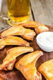 Smoked chicken wings with spicy sauce and glass of beer Stock Images