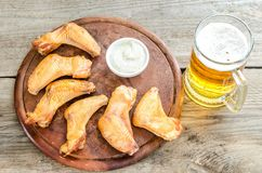 Smoked chicken wings with spicy sauce and glass of beer Royalty Free Stock Photo