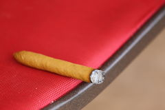 Smoked Cigar. A close up view of a cigar burning laying on a chair Stock Image