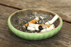 Smoked cigarettes. In green ashtray Royalty Free Stock Photography