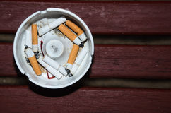 Smoked cigarettes in white ashtray on wood table Stock Photo