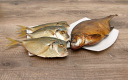 Smoked and dried fish closeup on wooden background. Stock Photos