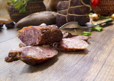 Smoked dried gammon ham and slices of sausages with bread, tomatos, herbs, garlic and basketson wooden board Royalty Free Stock Images