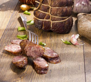 Smoked dried gammon ham and slices of sausages with bread, tomatos, herbs, garlic and basketson wooden board Stock Photos