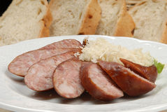 Smoked/dry sausage with horse radish on a white plate with bread in background Royalty Free Stock Image