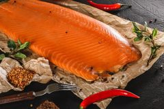 Smoked fillet salmon, red fish steak with spices and lemon on craft paper over dark stone background. Tenderloin fish still life,. Seafood, top view stock photography