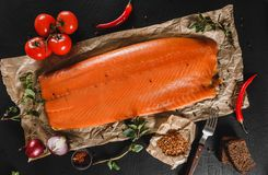 Smoked fillet salmon, red fish steak with spices and tomato on craft paper over dark stone background. Tenderloin fish still life. Seafood, top view, flat lay stock images