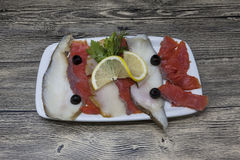 Smoked fish delicacies from the Northern seas halibut, salmon.Slices of smoked salmon and halibut on a plate with a slice of lemon Royalty Free Stock Images