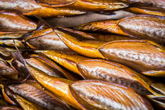Smoked fish in different sizes laying on a table Royalty Free Stock Images