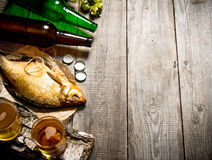 Smoked fish and fresh beer on a wooden table. Free space for text. Royalty Free Stock Photo