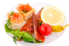 Smoked fish. With fresh vegetables and lemon on plate Stock Image
