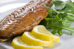 Smoked fish with lemon and salad Royalty Free Stock Photography