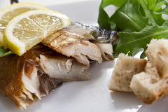 Smoked fish with lemon and salad Royalty Free Stock Photo