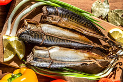 Smoked fish mackerel on a cutting Board on a background of vegetables. Royalty Free Stock Photos