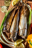 Smoked fish mackerel on a cutting Board on a background of vegetables. Stock Photography