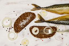 Smoked fish (mackerel, Scomber) on white background with rye bre Royalty Free Stock Photo