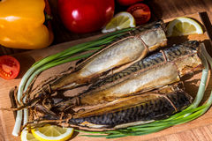 Smoked fish mackerel on wooden cutting board Stock Images