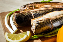 Smoked fish mackerel on wooden cutting board Stock Photo