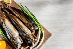 Smoked fish mackerel on wooden hardboard on wooden table. Royalty Free Stock Photo