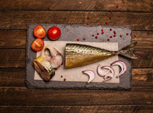Smoked fish with onion, tomato and pepper. Food background.