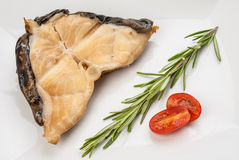 Smoked fish. A piece of smoked fish with Rosemary and tomatoes Stock Photo