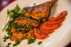Smoked fish on the plate with fresh tomato slices Royalty Free Stock Photo