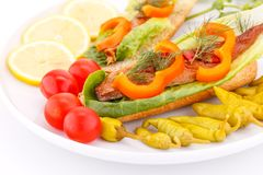 Smoked fish on plate. Smoked fish with fresh vegetables on plate Royalty Free Stock Photo