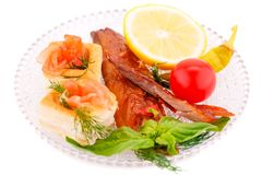 Smoked fish. With fresh vegetables and lemon on plate isolated on white background Royalty Free Stock Photos