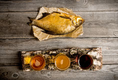 Smoked fish and three fresh beers on the birch stand. On a wooden table. Stock Image