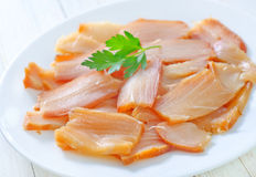 Smoked fish. On white plate Royalty Free Stock Photo